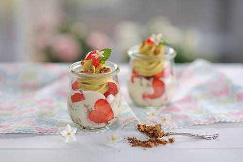 Veganes Bananen-Dattel-Granola-Dessert auf Joghurt, frischen Erdbeeren und Mango-Cashew-Creme