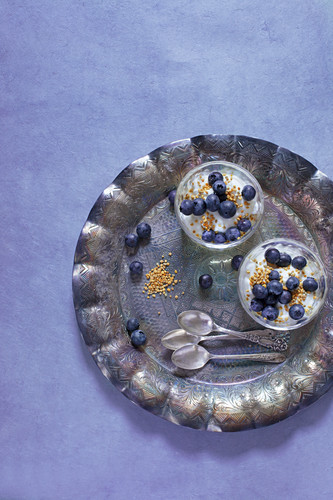 Two Glass Bowls of Plain Yoghurt with Blueberries and Bee Pollen on a Silver Tray