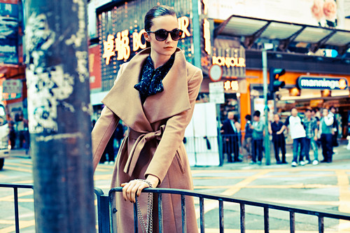 A young woman on a pavement wearing sunglasses and a camel-coloured coat
