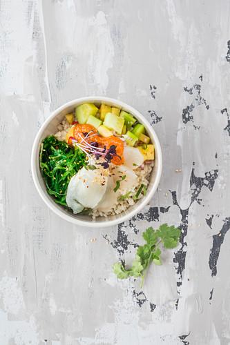 Poke bowl with black halibut, sushi rice, marinated algae and pineapple and cucumber salad served with sukiyaki sauce and sesame seeds (Hawaii)
