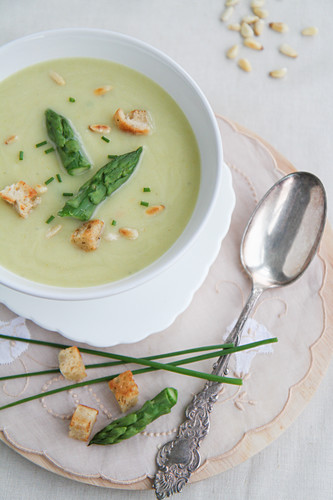 Cream of asparagus soup with croutons and pine nuts