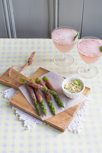 Green asparagus wrapped in ham with bearnaise sauce and strawberry cocktails