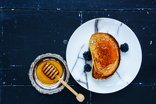 Breakfast theme. Grilled whole grain toasts with honey and fresh blackberries on vintage wooden background