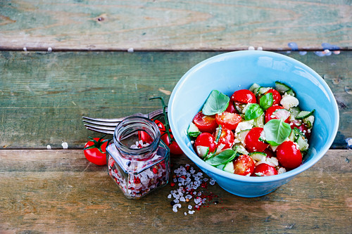 Organic summer vegetables and feta cheese salad in bowl on grunge wooden background, selective focus