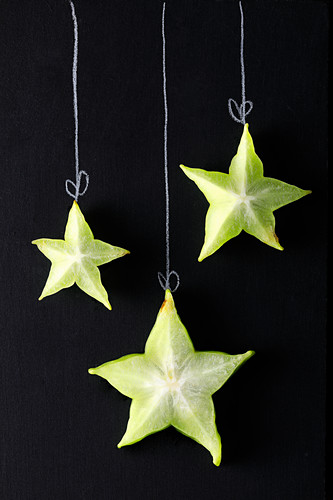 Slices of starfruit arranged on a blackboard to look like Christmas decorations