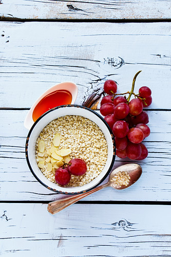 Quinoa flakes, honey, almonds and grapes for healthy breakfast on white wooden background
