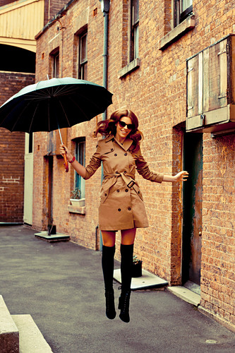 A brunette woman with an umbrella wearing a tench coat, overknee socks and ankle boots