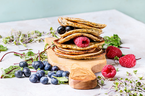 Stack of vegan chickpea pancakes on olive wood cutting board with green salad, sprouts, berries, over grey kitchen table