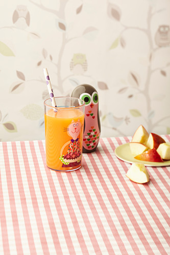 ACE vitamin juice for children in a colourful glass with a straw