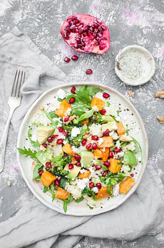 Winter salad made with millet, arugula, roasted sweet potatoe, pomegranate, broccoli, avocado, walnuts and feta cheese
