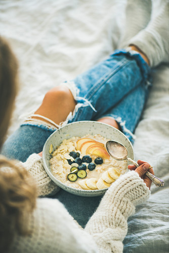 Woman in woolen sweater and jeans eating vegan almond milk oatmeal porridge with berries, fruit and almonds