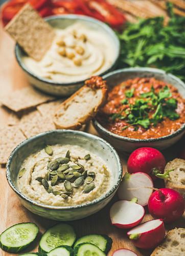 Various Vegetarian dips: hummus, babaganush and muhammara with crackers, bread and fresh vegetables, wooden background