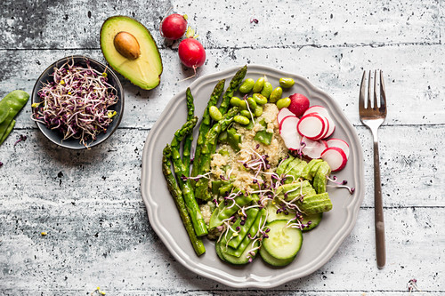 A green salad plate with bulgur wheat, asparagus, avocado, radishes, cucumber, mangetout, edamame and red sprouts