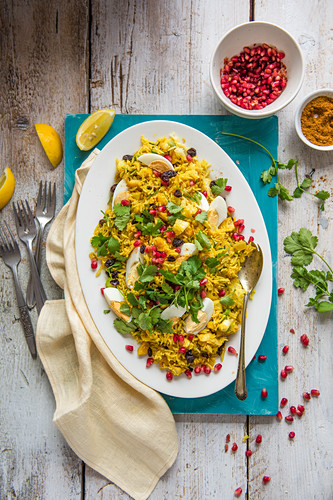 Kedgeree, curry spiced riced with smoked fish, egg, raisins, coriander and pomegarnate, view from above