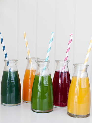 Individual jars of fresh pressed juices with straws (spirulina, orange carrot turmeric, spinach, beet and lemon ginger)