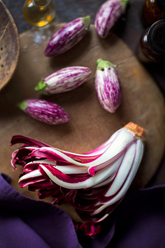 An arrangement of of trevisio and small aubergines on an old wooden board