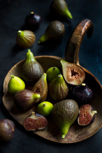 Three types of organic figs on an old wooden board