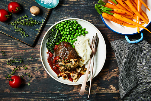 A slow cooked beef joint with red wine and mushroom sauce, mashed potatoes and peas