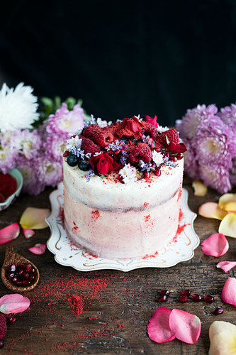 A red velvet layer cake topped with raspberries