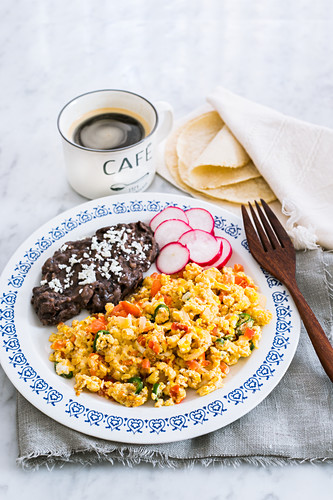 Huevos a la mexicana - Mexican scrambled eggs with tomatoes, onions and green chilli peppers served with fried beans, tortillas and coffee (tipical mexican breakfast)