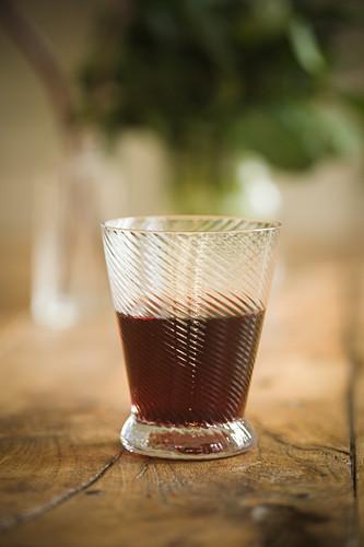 Glas Rotwein auf Holztisch