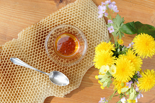 A bowl of honey on honeycomb and a bunch of meadow flowers