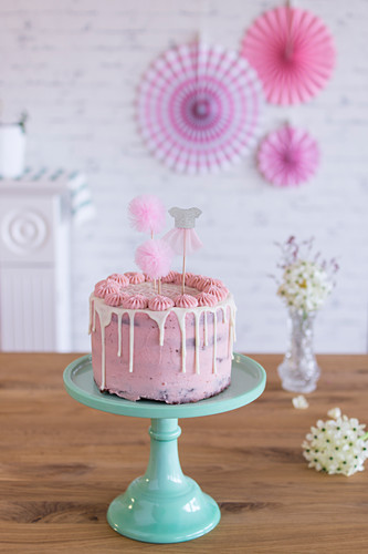Pink birthday cake with party decorations