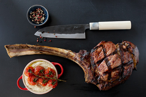 Grilled tomahawk steak with celery puree and tomatoes