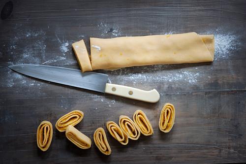 Süsser Nudelteig mit Orangen- und Zitronenabrieb am Stück und in Bandnudeln geschnitten