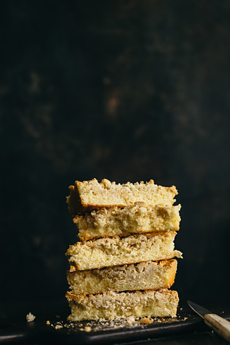Several lices of crumb cake, stacked against a dark background