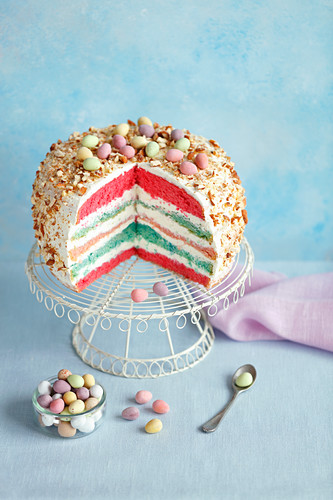 An Easter layer cake decorated with sugared eggs, sliced
