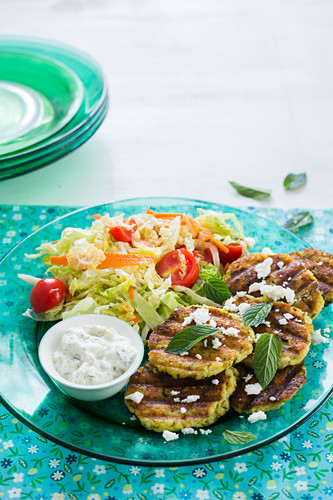 A green plate with zucchini, mint and feta grilled patties garnished with mint leaves and crumbled feta