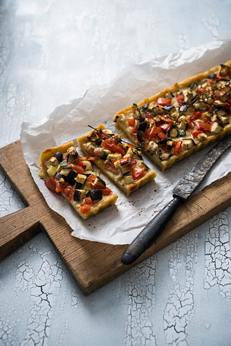 A vegan potato quiche with tomatoes, aubergines and courgette