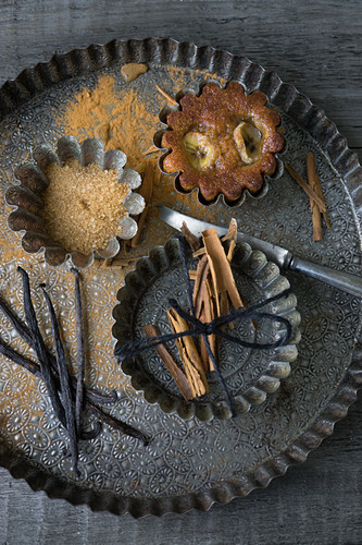 A banana muffin in a tin next to cinnamon, sugar and vanilla