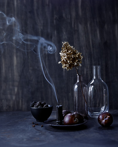 Still-life arrangement with smoking candle, autumn fruits and dried flowers in vase