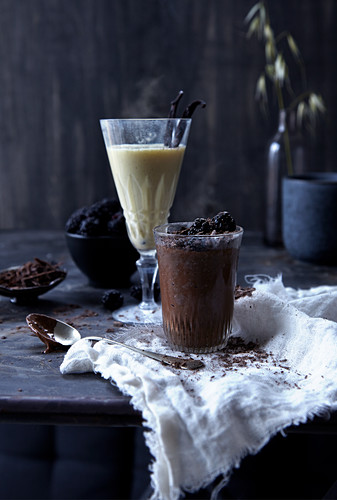 Dark chocolate pudding and a hot vanilla drink in glasses