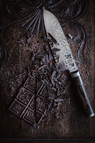 Chopped chocolate with a knife on a wooden surface (seen from above)