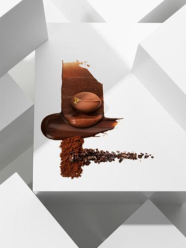 A chocolate praline on various chocolate textures
