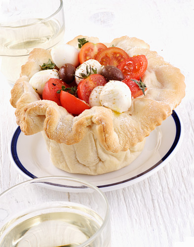 Tomatoes with mozzarella and olives in a bread owl