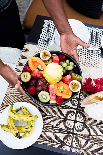 Schale mit exotischem Obst auf Tisch stellen