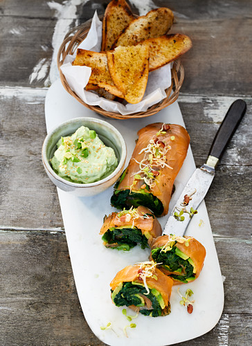 Avocado and salmon rolls with oriental herbs, a cream cheese and wasabi dip and grilled bread