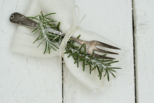 A napkin with a silver fork and a sprig of rosemary
