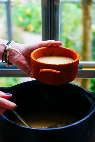 A person filling a bowl with soup from a pot