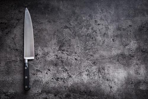A kitchen knife on a grey background