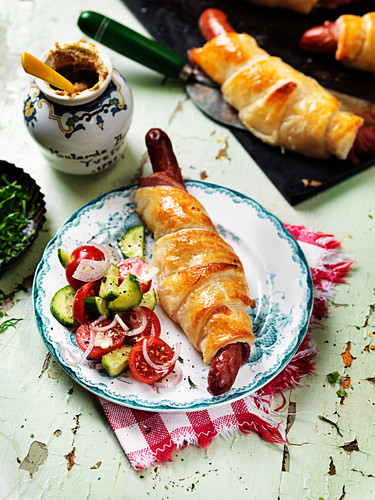 Sausages in puff pastry with tomato and cucumber salad