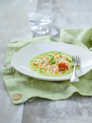 Ravioli with a tomato and olive filling on a courgette sauce with diced vegetables