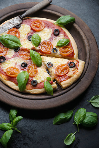 Vegan cauliflower pizza with tomatoes, olives, basil and vegan cheese