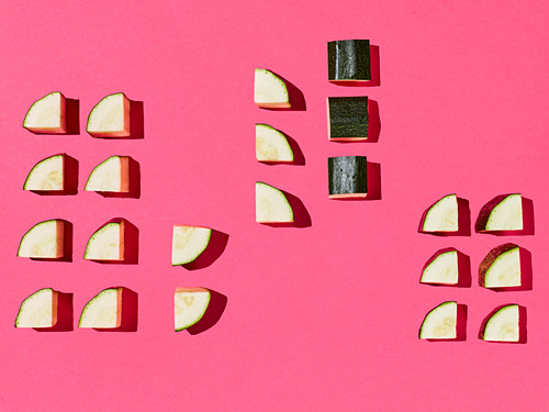 Quartered courgette slices on a pink surface