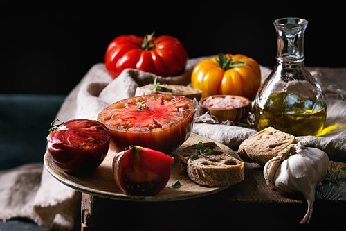 Red and yellow organic tomatoes with olive oil, garlic, salt and bread for salad or bruschetta