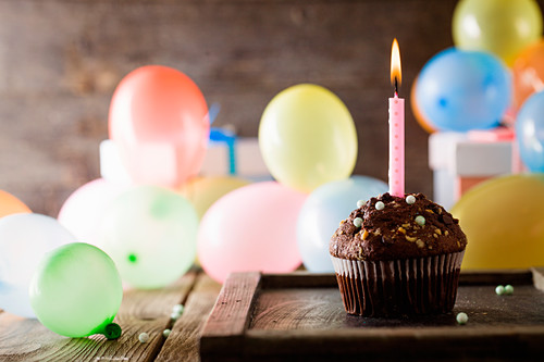 Frosted Chocolate Cupcake with a Lit Candy and Birthday Ribbon
